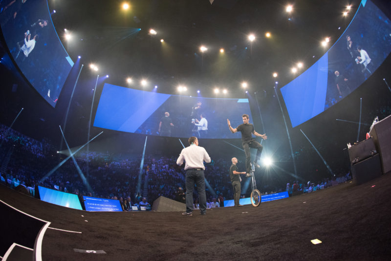 Jeff Civillico rides a unicycle in front of a huge audience.