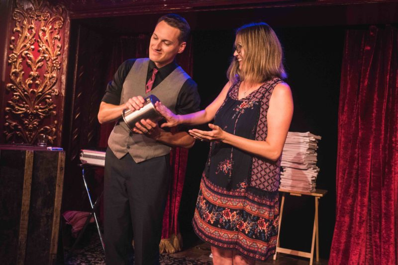 Corporate Comedy Magician Nick Paul with an audience member on stage.