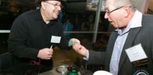 Wireman hands a custom bended wire to trade show attendee